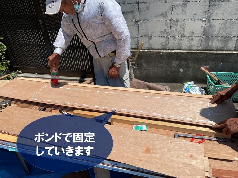 和歌山市の玄関庇の天井に無垢板をボンドで張り付けていきます