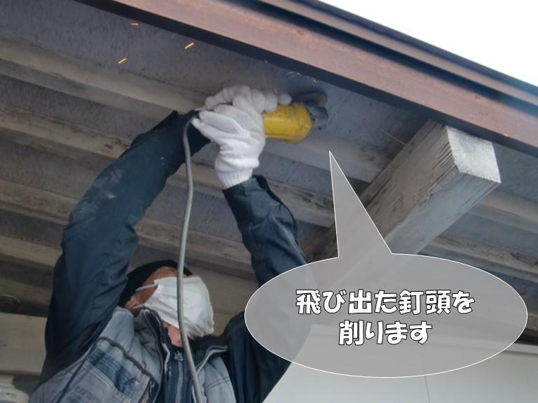 岩出市で倉庫の軒天を張り替える前に既存の軒天から出ている釘頭を削り落とします