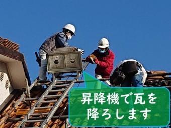 岩出市で屋根の葺き替え工事を行うのにセメント瓦を剥がし昇降機へ瓦を乗せて降ろしていきます
