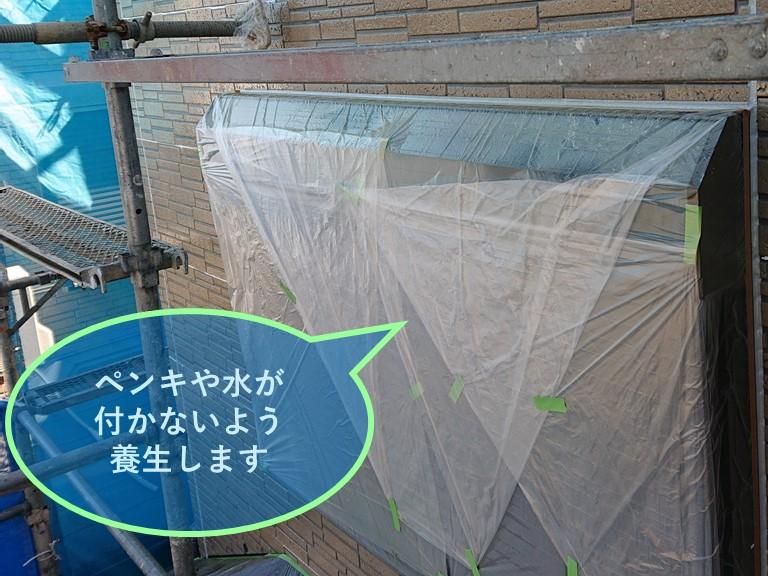 紀の川市での外壁塗装で塗装を始める前にペンキが付かないよう養生していきます