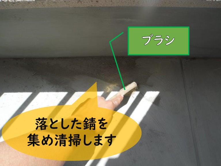 和歌山市で防水工事を行うのにケレン作業を行い落とした錆をブラシで集めて清掃しています