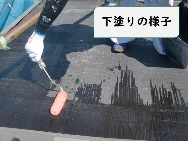 岩出市の屋根塗装の様子でローラーを使用し下塗りを行っている写真