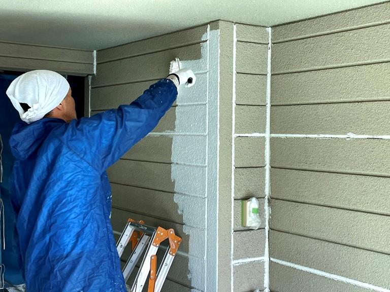 岩出市で外壁工事を行い、下地処理後の下塗り(フィラー)の様子で、外壁以外にも駐車場の壁も塗装していきます