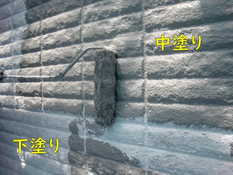 岩出市で多様模様の外壁塗装を行い表面が凸凹した外壁に中塗りを行っている写真